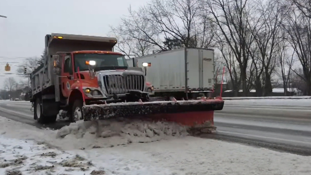 A snow plow clears snow from one side of a Delaware road as a big rig drives by on the other side.