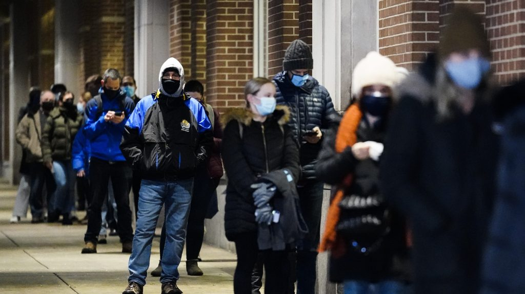 People wait in line at a COVID-19 vaccination site at the Pennsylvania Convention Center in Philadelphia, Wednesday, Feb. 3, 2021. The clinic opened to help provide second doses of COVID-19 vaccinations.