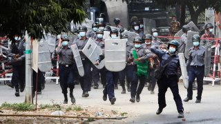 In this Feb. 20, 2021, file photo, police charge forward to disperse protesters in Mandalay, Myanmar. Security forces in Myanmar ratcheted up their pressure against anti-coup protesters Saturday, using water cannons, tear gas, slingshots and rubber bullets against demonstrators and striking dock workers in Mandalay, the nation's second-largest city.