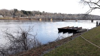 A deck sticks out from a grassy bank and overtop the waters of the Delaware River.