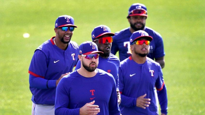 Texas Rangers outfielders from left, Leody Taveras, Joey Gallo, Adolis Garcia, Willie Calhoun and Delino DeShields, back right, run during spring training baseball practice, Friday, Feb. 26, 2021, in Surprise, Ariz.