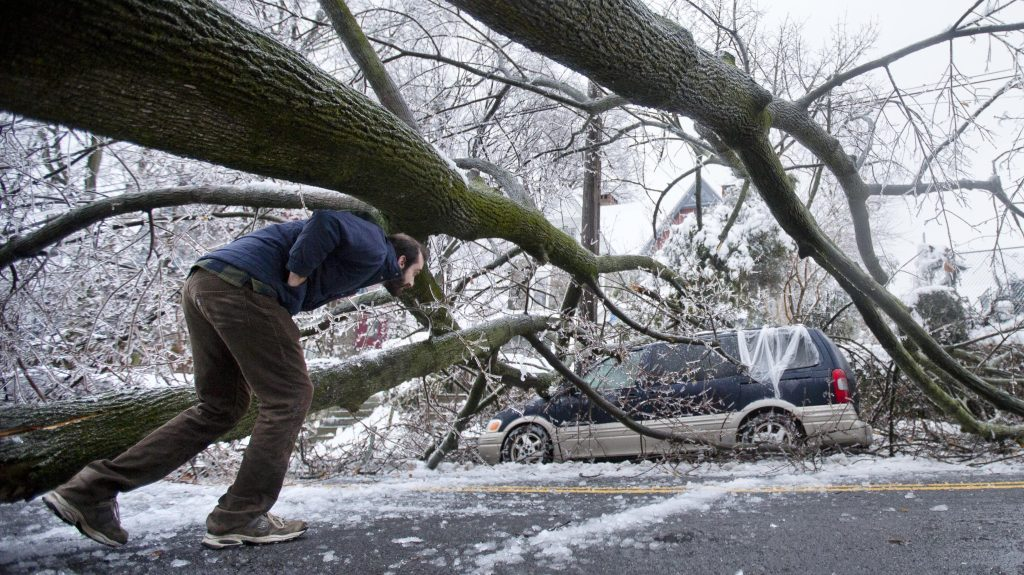 In this Feb. 5, 2014, a man inspects an ice covered downed tree that took out a utility line and landed atop a minivan, after a winter storm in Philadelphia.