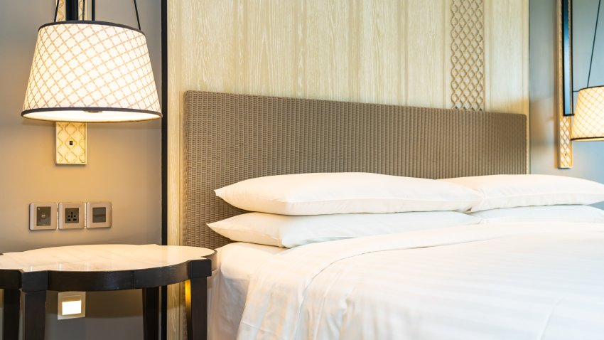 A lamp is turned on next to a made hotel bed