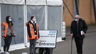 A man walks past volunteers at a temporary vaccination hub set up to administer a Covid-19 vaccine, at the Colchester Community Stadium in Colchester, Essex, south east England on February 6, 2021.