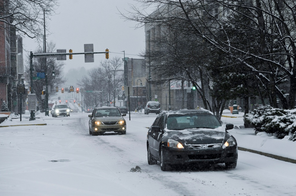 Cars make their way along a snow covered Penn Street in Reading, Pennsylvania