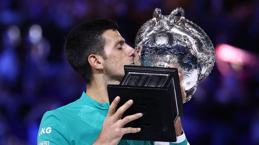 Novak Djokovic of Serbia holds the Norman Brookes Challenge Cup as he celebrates victory in his Men's Singles Final match against Daniil Medvedev of Russia during day 14 of the 2021 Australian Open at Melbourne Park on February 21, 2021 in Melbourne, Australia.