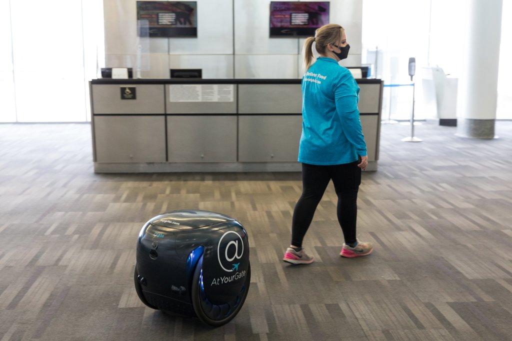 Photo courtesy of Philadelphia International Airport's gita robot and a woman