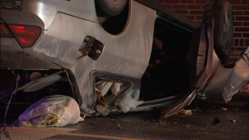 A silver car rests on its crushed roof after flipping over on an icy road in Philadelphia.