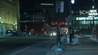 """An empty street is shown next to a sidewalk in Center City. Parking meters can be seen on the sidewalk. In the distance is a building with a neon sign reading """"Schuylkill"""""""