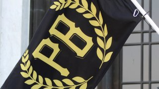"A flag with the letters ""PB"" surrounded by a golden wreath."
