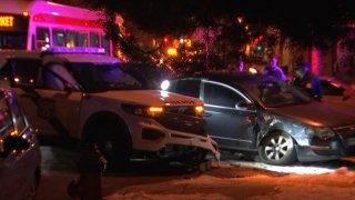 A Philadelphia police SUV rests next to a dark civilian sedan after a crash. Both vehicles have front-end damage.