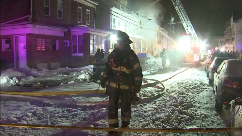 A firefighter walks along a Trenton, New Jersey, street. Behind him can be seen row houses on the left and parked cars on the right. In the middle of the street is a fire truck with its ladder expanded upward as firefighters douse a home with water from above.