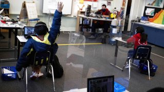 Chrystopher Camey Lopez raises his hand to ask a question from a socially-distanced desk during an in-person hybrid learning day at the Mount Vernon Community School in Alexandria, Virginia,