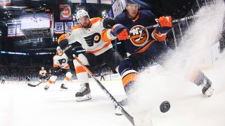 The Flyers and Islanders fight over the puck