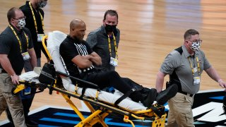 Referee Bert Smith is taken off the court on a stretcher after collapsing during the first half of an Elite 8 game between Gonzaga and Southern California during the first half of an Elite 8 game in the NCAA men's college basketball tournament at Lucas Oil Stadium, Tuesday, March 30, 2021, in Indianapolis.