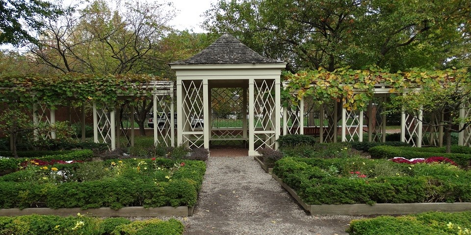 A walkway surrounded on both sides by green plants leads to a gazebo at the 18th century garden in Philadelphia's Independence Hall