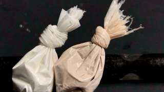 Cocaine and heroin in bags with stem in background