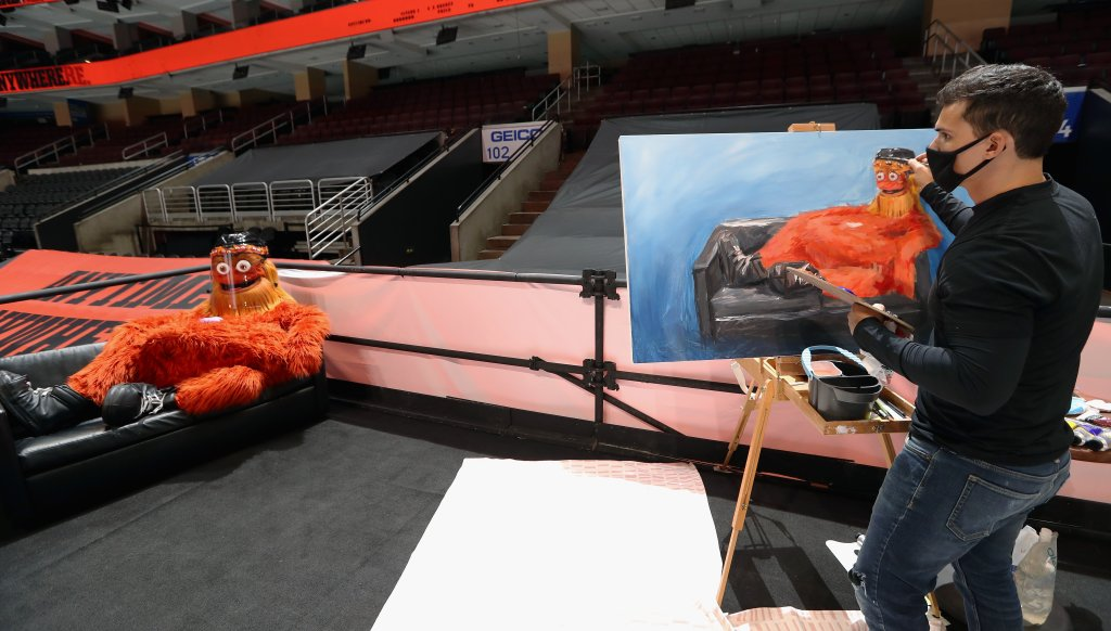 Gritty poses for a painting as an artist paints the Flyers mascot