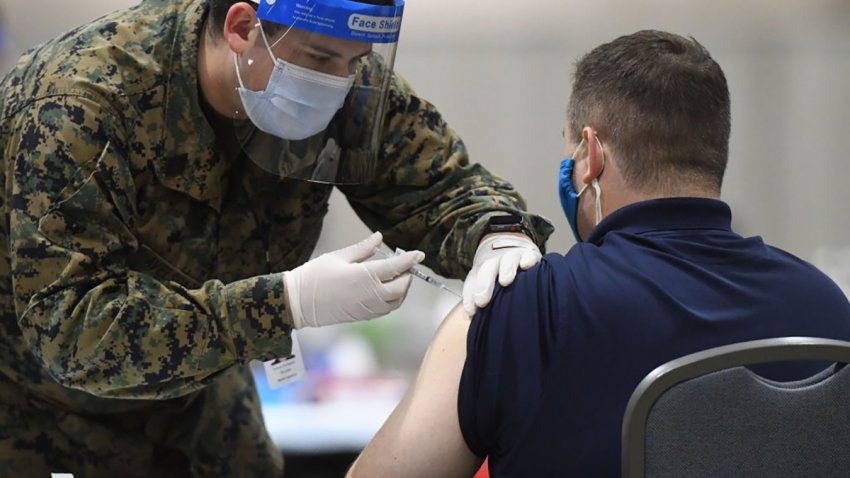 A member of the U.S. Armed Forces administers a COVID-19 vaccine to a police officer at a FEMA community vaccination center on March 2, 2021 in Philadelphia,