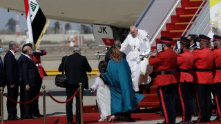 Pope Francis walks down the steps of an airplane as he arrives at Baghdad international airport, Iraq, Friday, March 5, 2021. Pope Francis heads to Iraq to urge the country's dwindling number of Christians to stay put and help rebuild the country after years of war and persecution, brushing aside the coronavirus pandemic and security concerns.
