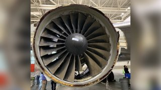 This photo provided by The National Transportation Safety Board shows the damaged engine of United Airlines Flight 328.