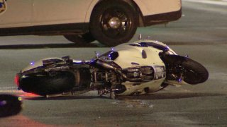 A motorcycle rests on its side on the pavement after a deadly crash in Philadelphia's West Oak Lane neighborhood.