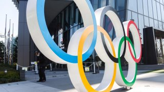 A man wearing a face mask stands behind the Olympic symbols of the five interlaced rings pictured near the National Stadium in Tokyo.
