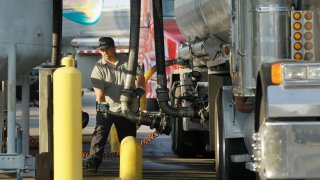 A man moves a fuel hose into position to begin loading gasoline into a tanker truck