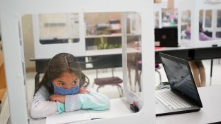 Second grader Londyn Vargas does her school work at Christa McAuliffe School in Jersey City, New Jersey, Thursday, April 29, 2021. Kindergarten through third grade students are returning to their school buildings in Jersey City for their first time in over a year.