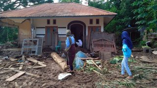 Indonesian women walk past a house damaged by flood in Waiwerang, on Adonara Island, East Nusa Tenggara province, Indonesia, Tuesday, April 6, 2021. Rescuers in remote eastern Indonesia were digging through the debris of a landslide Tuesday in search of people believed to be buried in one of several disasters brought on by severe weather in the Southeast Asian nation and neighboring East Timor.