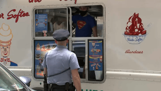 A Philadelphia police officer stands in front of a truck and orders ice cream.