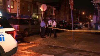 Philadelphia police officers stand at a West Philadelphia street corner near where a man was gunned down.