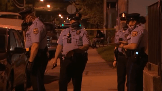Philadelphia police officers stand at the scene where a 10-year-old boy was grazed by a bullet.