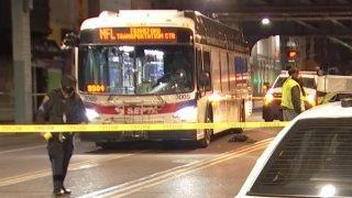 Crime scene tape surrounds a SEPTA bus as investigators walk around the street following a crash that killed a pedestrian in Philadelphia's Frankford neighborhood.