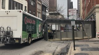 A wooden pod sits next to a box truck in the middle of a Philadelphia street after the truck struck and dragged the pod.