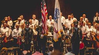An orchestra with three servicemembers holding flags