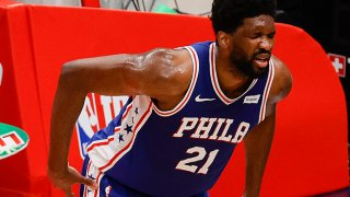 Joel Embiid holds his back