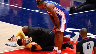 Basketball players and officials look at a man lying on a basketball court