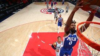 A basketball player dunks