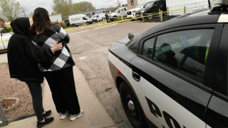 COLORADO SPRINGS, COLORADO - MAY 9: A neighbor, left, comforts a family member of some of the six shooting victims outside the scene of the shooting at the Canterbury Mobile Home Park on May 9, 2021 in Colorado Springs, Colorado. A gunman killed six people at a family birthday party before taking own life, police said. The victims were all members of the same extended family a party attendee said. The shooting was in the 2800 block of Preakness Way in the Canterbury Mobile Home Park. The shooting happened just after midnight. Colorado Springs police Lt. James Sokolik said in a news release. Investigators believe the shooter, who has not been publicly identified, was the boyfriend of a woman at the party.