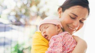 Mother carrying sleeping baby girl