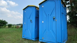 Two portable toilets rest on a field of grass.