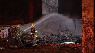Firefighters douse water on a blaze at an interstate underpass in South Philadelphia.
