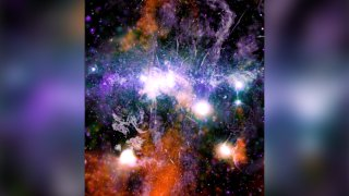 """NASA has released a stunning new picture of our galaxy's violent, super-energized """"downtown."""" It's a composite of hundreds of images taken by the orbiting Chandra X-ray Observatory over the past two decades. Astronomer Daniel Wang of the University of Massachusetts Amherst said Friday he spent a year working on this while stuck at home during the pandemic. The picture depicts billions of stars and countless black holes at the center, or heart, of the Milky Way. This busy, high-energy galactic center is 26,000 light years away. Launched in 1999, Chandra is in an extreme oval orbit around Earth."""