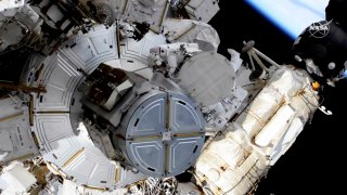 In this image taken from NASA video, French astronaut Thomas Pesquet, top center, and NASA astronaut Shane Kimbrough venture out on a spacewalk Wednesday, June 16, 2021, to outfit the International Space Station with powerful, new solar panels to handle the growing electrical demands from upcoming visitors.
