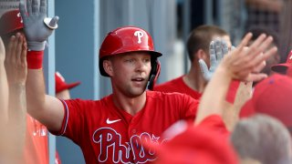 Rhys Hoskins high fives Phillies teammates while wearing a red jersey