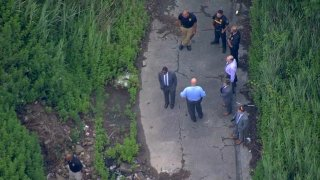 Law enforcement gather near a site where a woman's body was discovered in Chester, Pennsylvania, on June 22, 2021.