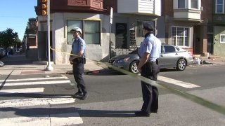Two Philadelphia police officer stand behind crime scene tape as they block off a street where a 16-year-old boy was shot.