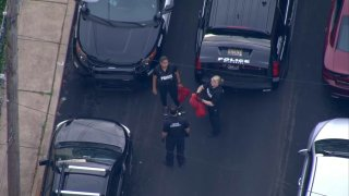 An aerial view shows three police officers holding red bags on a street near where a 14-year-old boy was shot to death in Wilmington.