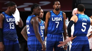 """Members of the U.S. men's basketball team stand in blue jerseys with the letters """"USA"""" across the front."""